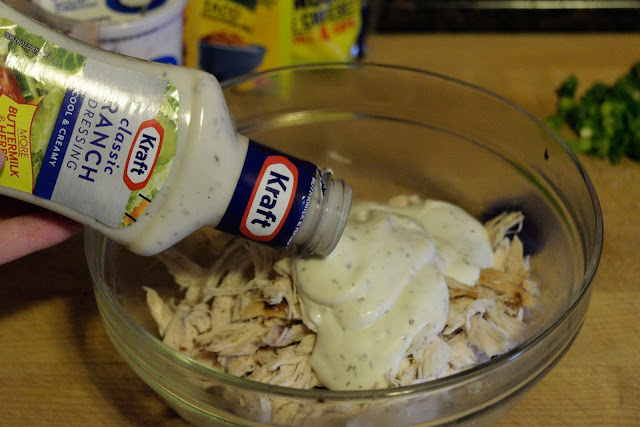 A picture of shredded chicken, in a bowl, with ranch dressing being poured over it.