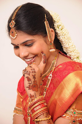 Cute smile by Indian bride Ananya decorated by ornaments.