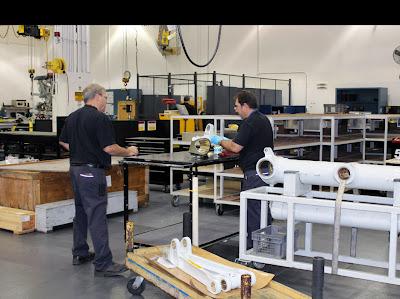 Funcionários em processo da manutenção de peças de aeronaves.