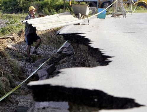 These 16 photos will disturb you... The Balkans in the grip of flood! - A man is seen next to a damaged road as he collects building materials after heavy floods in Bosanski Samac May 19, 2014.