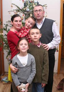 Szöveg: Együtt a Dimény család. Kép: Családi kép karácsonyfa előtt. Anya ölében a kisebbik fiú, aki grimaszol, apa előtt a nagyfiú, akinek a vállán nyugszik az apja keze, a nagyfiú előtt, srégen az anya előtt meg a lány, akit a nagyfiú átölel, s akinek a kezében egy plüssállatka van.