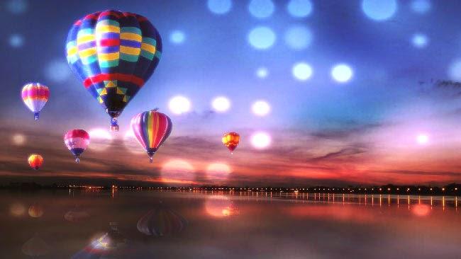 Na imagem, há alguns balões coloridos sobre um grande lago. Ao fundo, alguns pontos de luz da cidade.