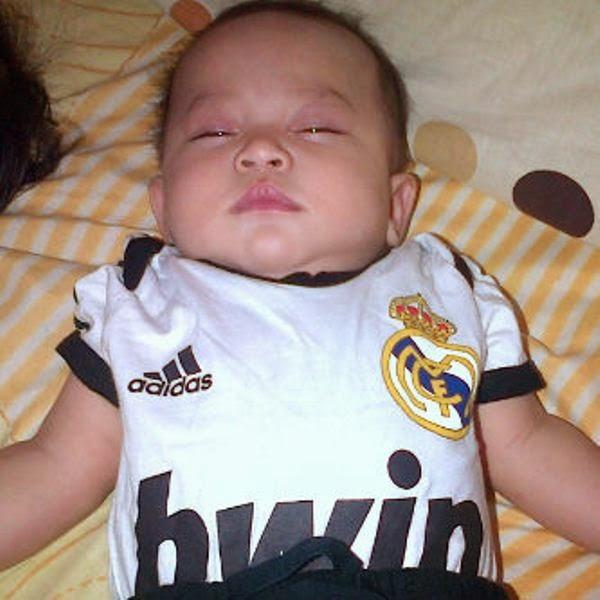Foto bayi lucu pakai seragam sepak bola real madrid lagi tidur