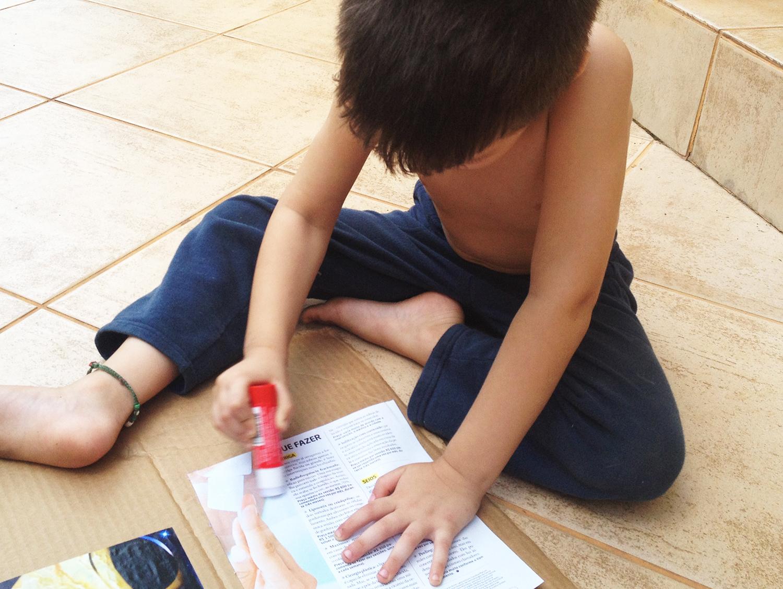 Miguel colando a página da revista no papelão