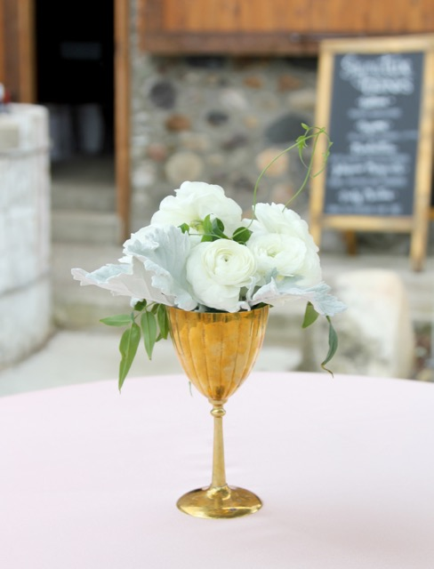 Vintage Brass Goblet cocktail table floral arrangement with white ranunculus dusty miller and jasmine vine.  Misty Valley Sweet Pea floral Design Ann Arbor Detroit
