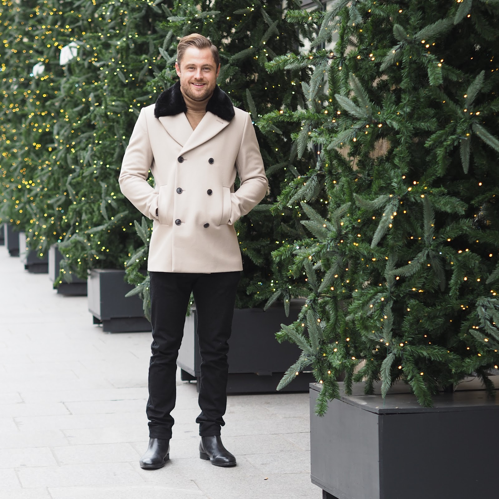 Man in fur trimmed coat standing next to line of christmas trees, paris
