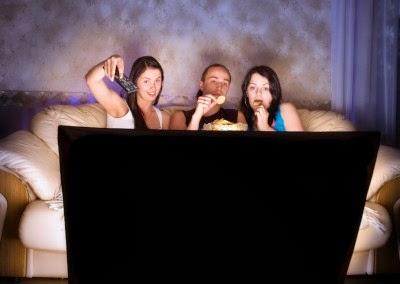 tres personas en el sofa viendo la tele