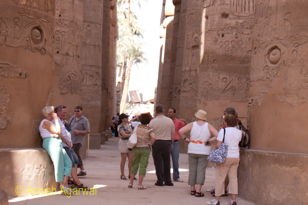 Tourists at the base of pillars inside the Hypostyle Hall in the Karnak temple