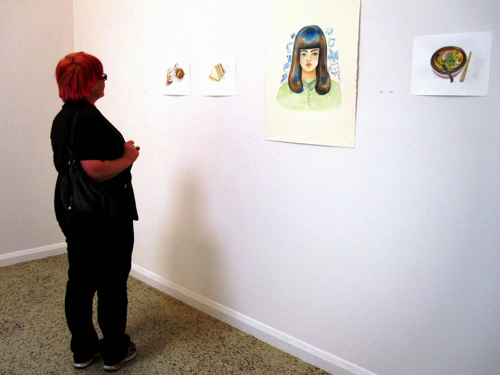 Woman standing in front of several coloured sketches in a gallery.