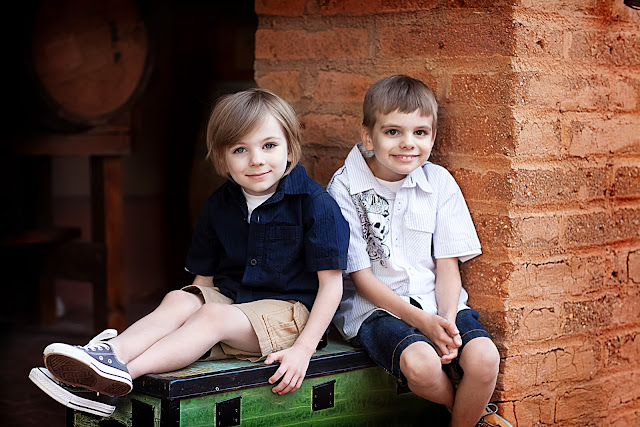Handsome male children sitting next to each other smiling for a portrait