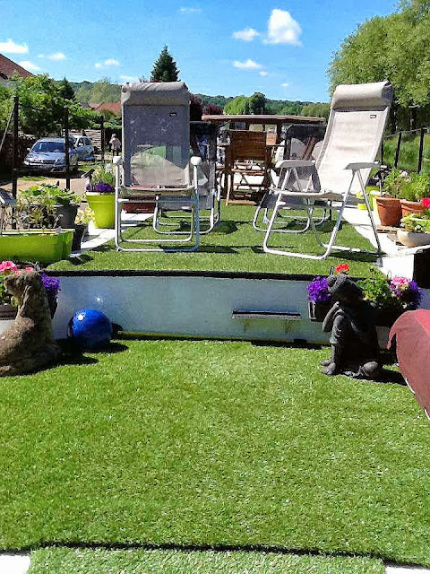 A large area of deck garden with beautifully soft AstroTurf, lounges, deck chairs, a giant beanbag and an outside table with six chairs for al fresco dining.