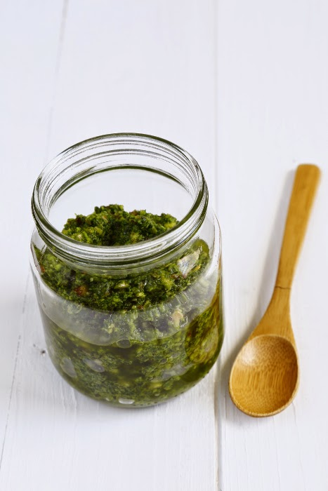 A jar of pesto with a wooden spoon on a white background