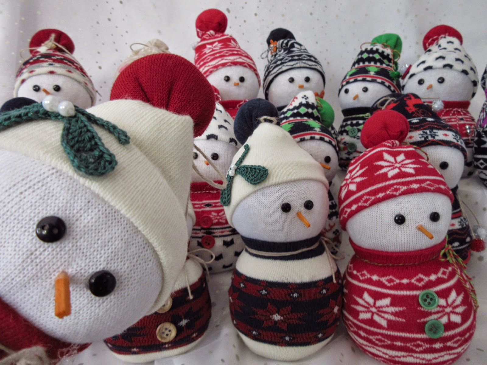 Crowd of snowmen made from socks filled with rice with button eyes and craft stick noses.