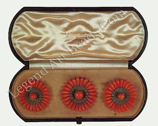 A pair of hair ornaments and a brooch by GIULIANO from the collection of Mrs. William Holman Hunt in the form of marguerites the petals carved from coral and the centers of enamel set with a coral bead. The signed brooch cannot be later than 1895 but the box dates from 1912 -14. It has been suggested by Mrs. Elizabeth Tompkin, adopted daughter of Qladys Holman Hunt and current owner of the jewels, that the date of the box might be explained if the combs, which are unsigned, were made between 1912 and 1914 to match the existing brooch.
