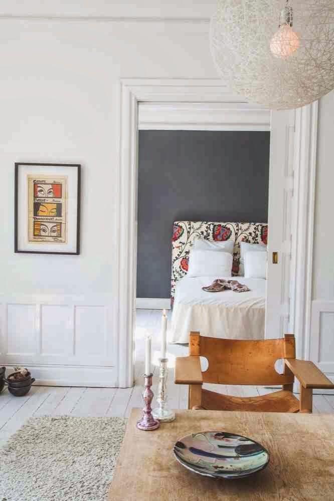 Widok z białego salonu na szarą sypialnię, drewniane kzresło z oparciami