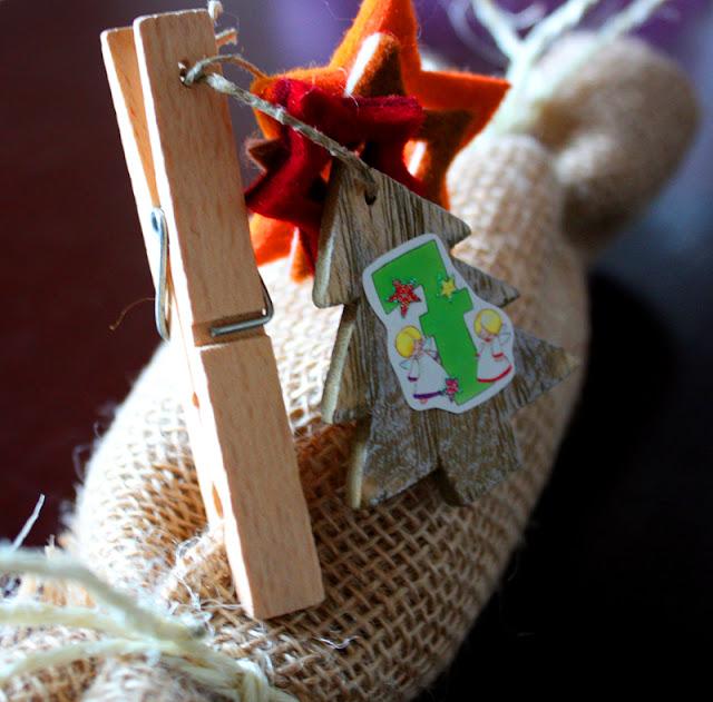 Adventskalender, Geschenk in Sackleinen eingepackt, mit kleinem Tannenbaum-Anhänger aus Holz und ausgestanzten Filzsternen befestigt an einer Holzwäscheklammer