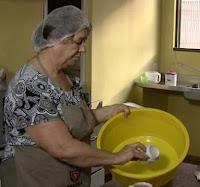 Foto da agricultora Mailde Otembra preparando a receita de pão de mandioca