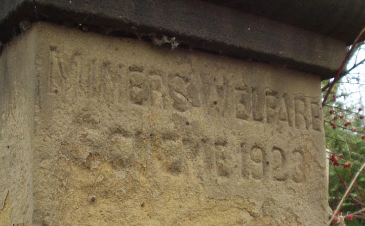 "The top of a sandstone gatepost, there's a capping stone overshadowing very worn carved letters.  ""Miners Welfare Square 1923""."