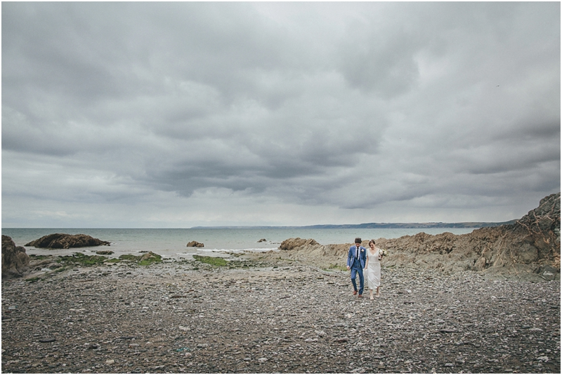 Bride and groom walking across beach