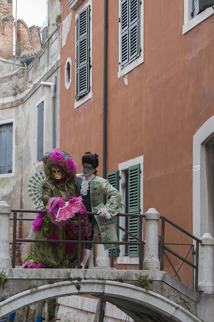 costumed couple on a bridge in Venice