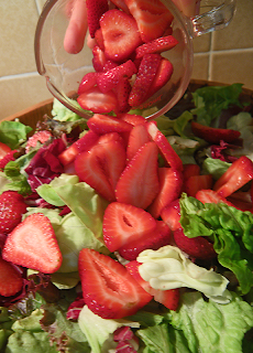 Cup of Sliced Strawberries Being Poured into Salad