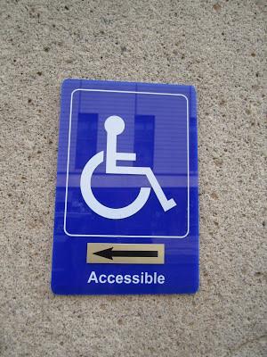 Pictograma de usuario de silla de ruedas con flecha direccional y rótulo de Accesible en relación con la dirección de la flecha.