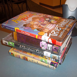 Stack of books on the counter at Bellview Elementary School library: True Things (Adults Don't Want Kids to Know) by Jimmy Gownley, Magyk by Angie Sage, A Christmas Carol by Charles Dickens, Animorphs: Visser by K.A. Applegate, Animorphs: The Capture by K.A. Applegate and The Underneath by Kathi Appelt
