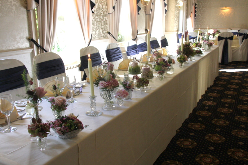 along the front of the top table containing flowers candles tealights