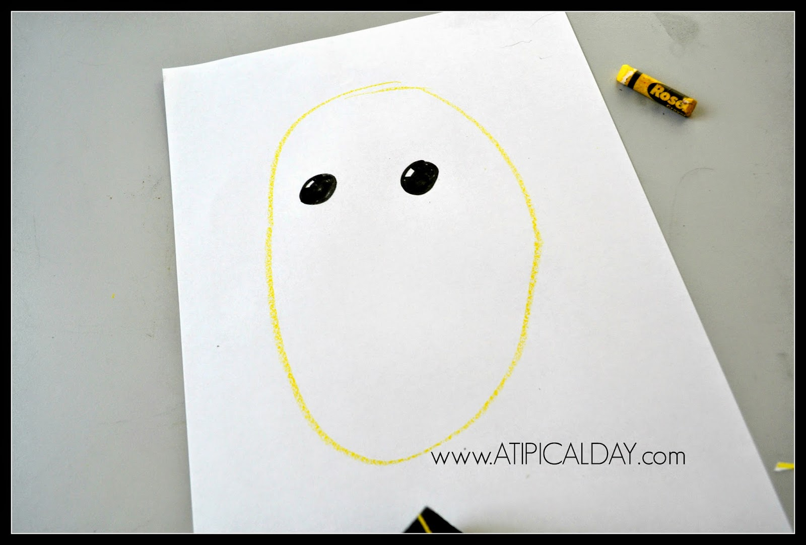 A piece of white paper with a yellow circle and 2 black eyes