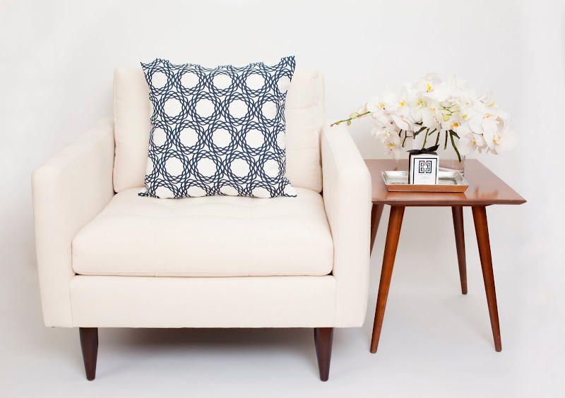 COCOCOZY Cotton Collection pillow in Oxford on a white armchair next to a wood side table with a COCOCOZY candle on a silver dish and an orchid flower arangement