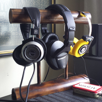 bamboo headphone stand with three headphones on it
