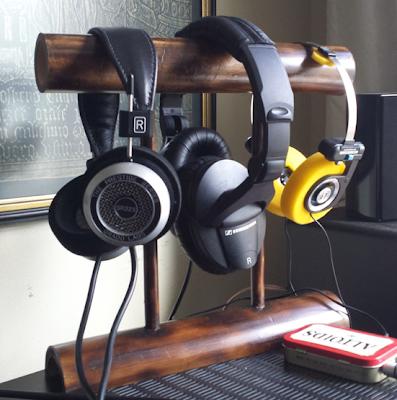 bamboo headphone stand with three headphones on it