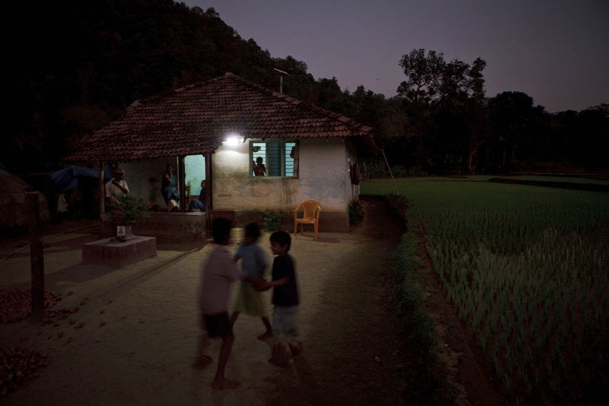 Lights powered by a solar unit illuminate a house in a village in Karnataka, India. Prime Minister Narendra Modi wants to bring electricity to every home by 2019 by leapfrogging the nation's ailing power-distribution infrastructure with solar-powered local networks.  (Credit: Kuni Takahashi/Bloomberg)  Click to enlarge.