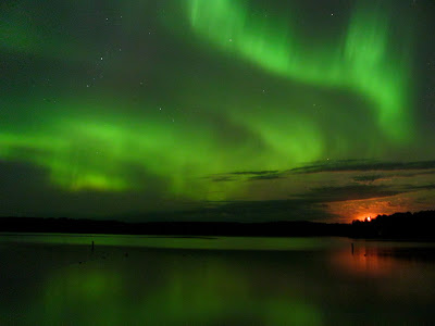 The moon looks orange as it rises. The greenish Aurora Borealis is reflected in a lake.