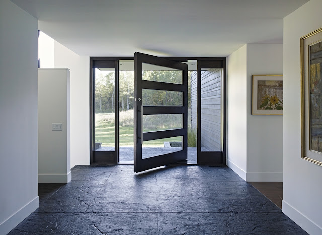 Picture of large black entrance doors as seen from the hallway inside