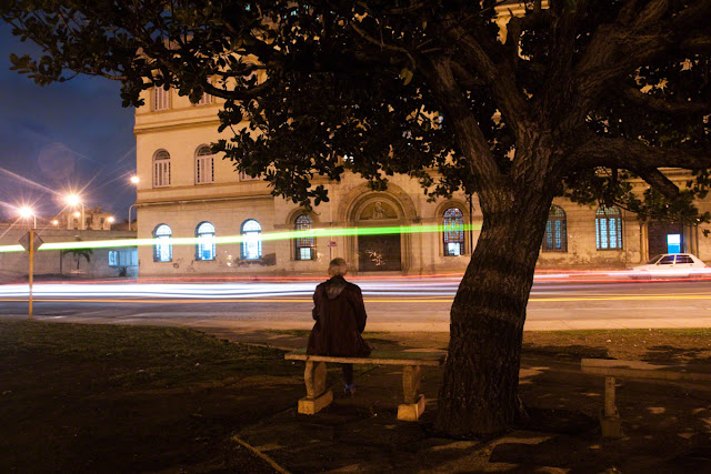 Havana, Cuba a man watching traffic go by at night by Marlon Krieger