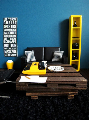 Modern dolls' house miniature lounge with blue walls, black sofa with black and white striped cushions, a winter-themed bus destination roll print and a yellow and white vase. On the pallet coffee table is a typewriter and paper.