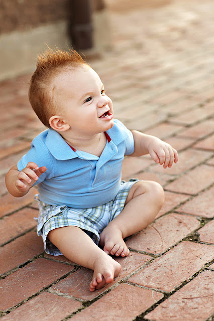 Tucson baby sitting on textured brick during family photo shoot