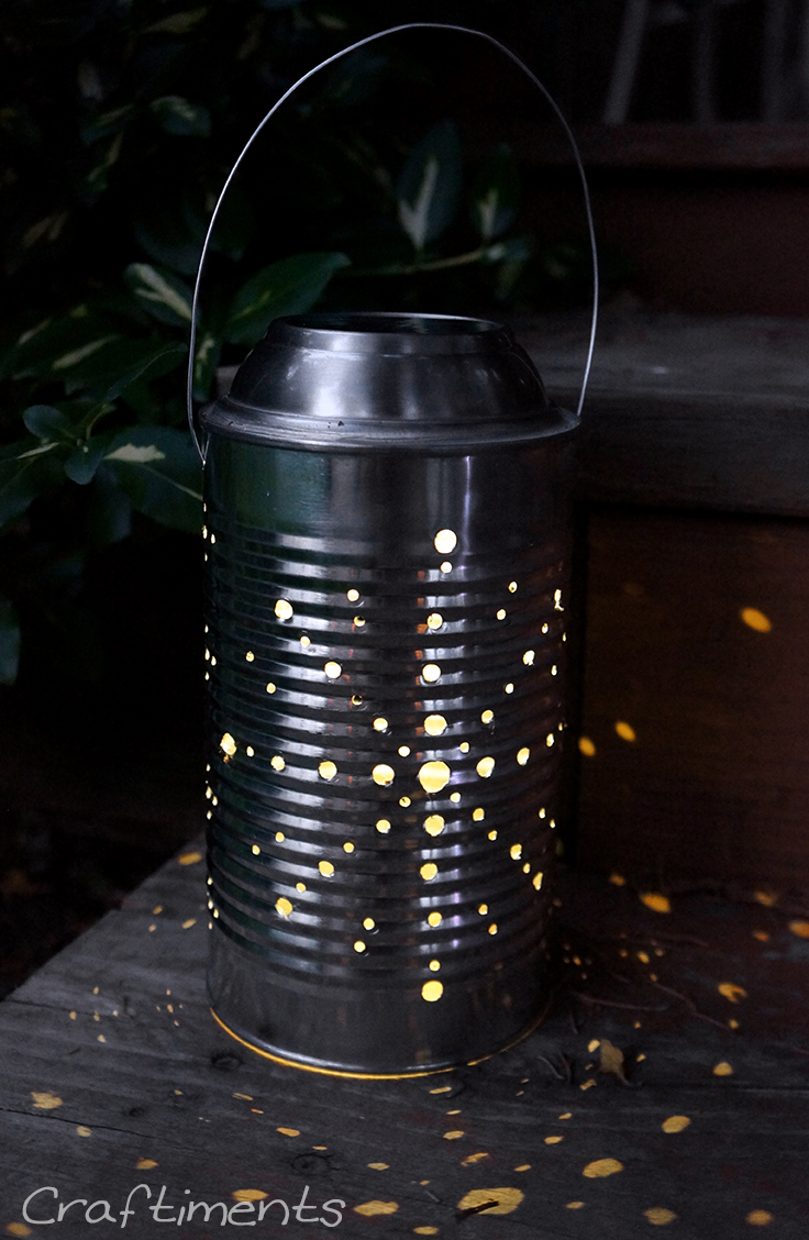 Tin can solar lantern sitting on steps.