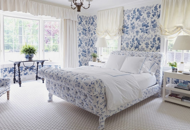Blue bedroom with upholstered blue and white floral sleigh bed and matching wallpaper