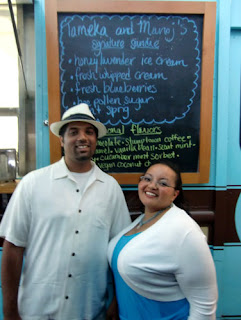 Manoj and Tameka in front of the Molly Moon sign with its wedding specialties