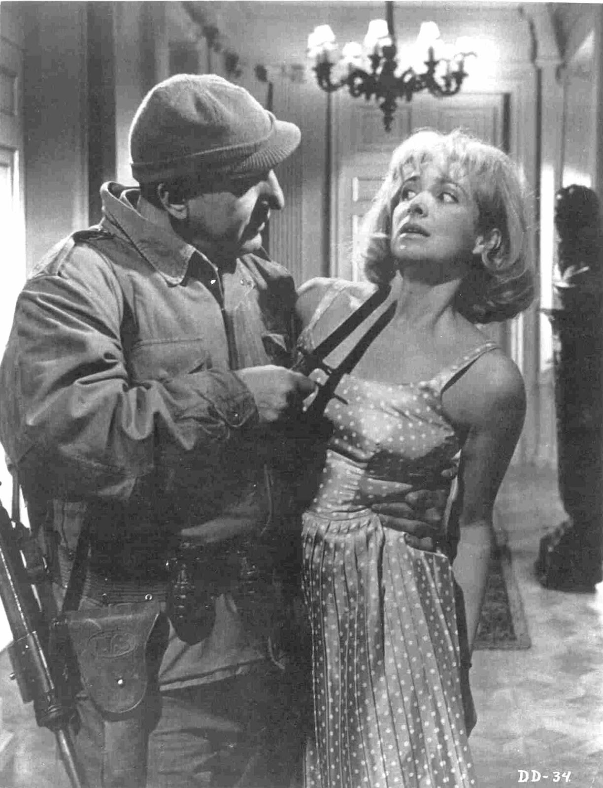 Telly Savalas menacing a German woman in The Dirty Dozen movieloversreviews.blogspot.com
