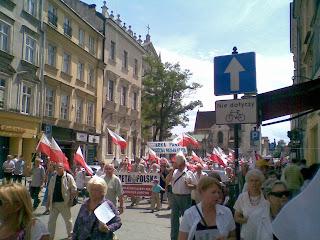 Anziani con bandiere e altoparlante alle spalle