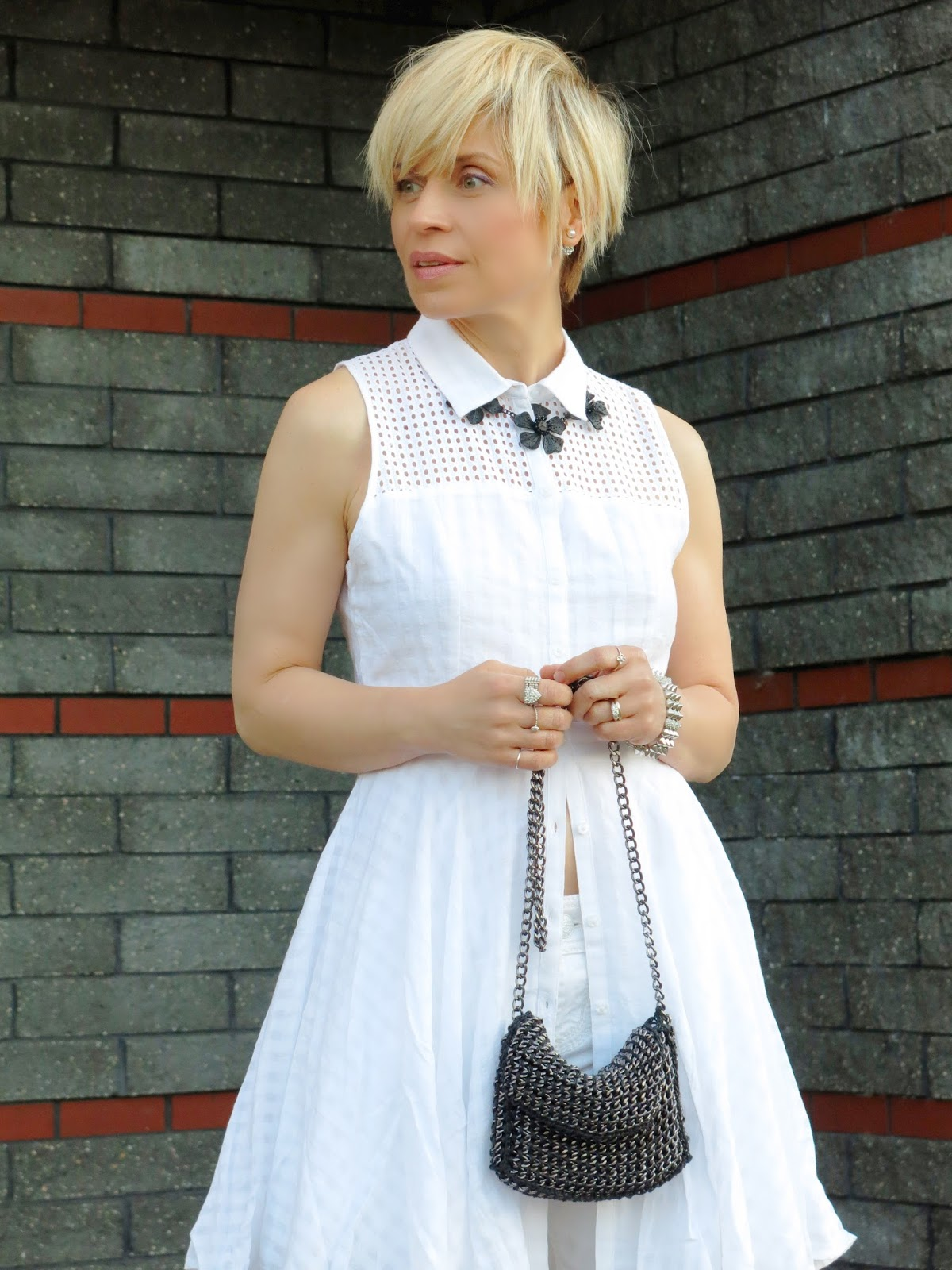 styling a white dress over white skinny jeans, with black pumps and a statement necklace