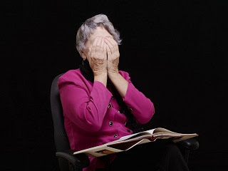 A elderly woman unable to concentrate with what she is reading