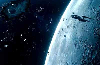 Plano del Vengance en la distancis, con restos de diverso tamaño flotando en todo el encuadre. La luna ocupa casi la mitad de la imagen, mostrándose solo de forma parcial, con una leve curvatura.