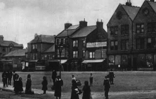 An old black and white photograph of shops, there is a large double gabled shop on the right, smaller shops running off to the left.  Children are playing in the foreground.