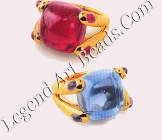 Two brightly colored 'candy' rings designed in the logos, one in pink tourmaline, the other in blue topaz.