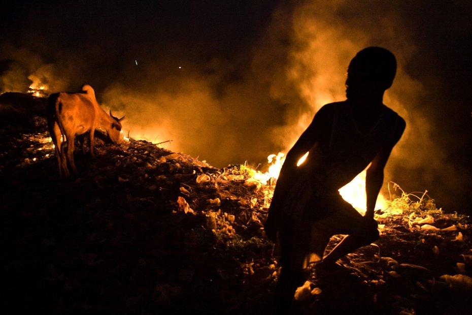El adolescente Amarou quemando basura en un vertedero de Niamey, Níger. [Fotografía: Alfredo Bini.]
