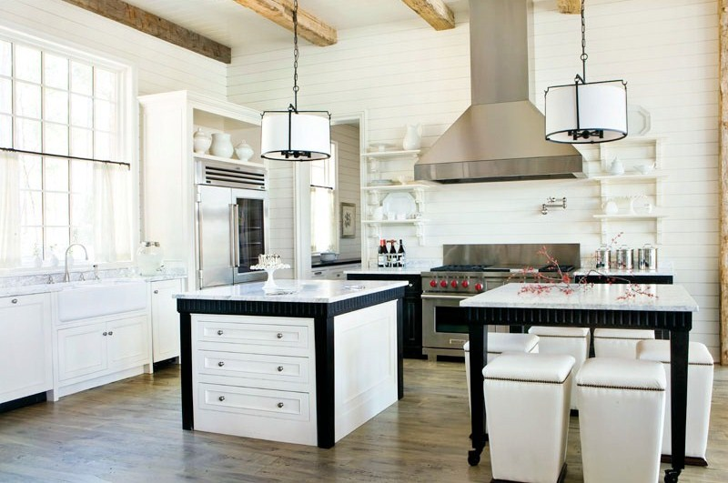 White rustic kitchen with stainless appliances, wood floor, two black and white pendant lights, Carrara marble countertops, and two islands one for preparing food which has white drawers and black detailing and the other for dining which is surrounded by white stools